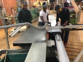 Abdi Rashid, Abdi Said och Ahmed justersågar längden på sittbrädor.